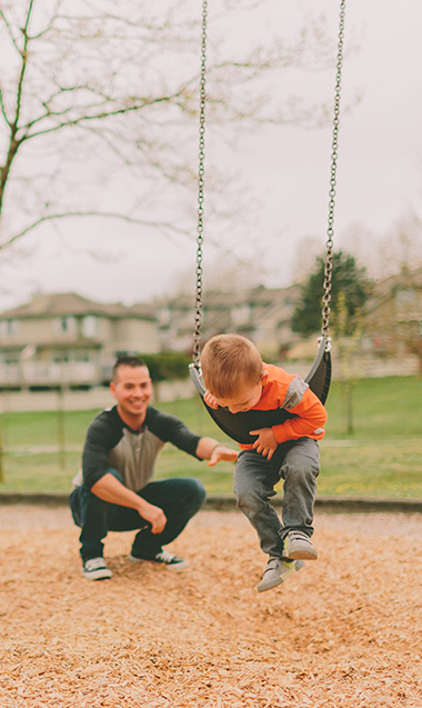 Young child swinging with his Dad