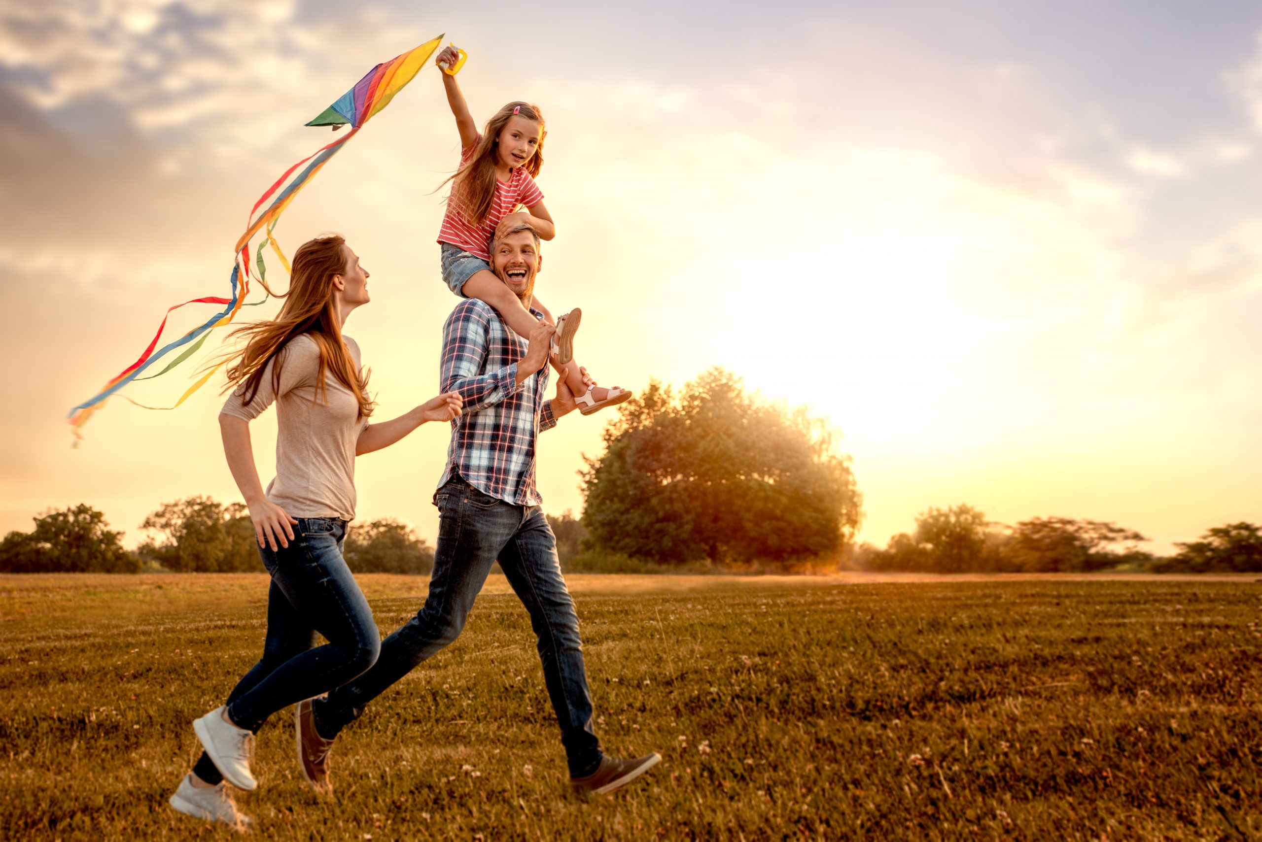 Kid flying kite with parents